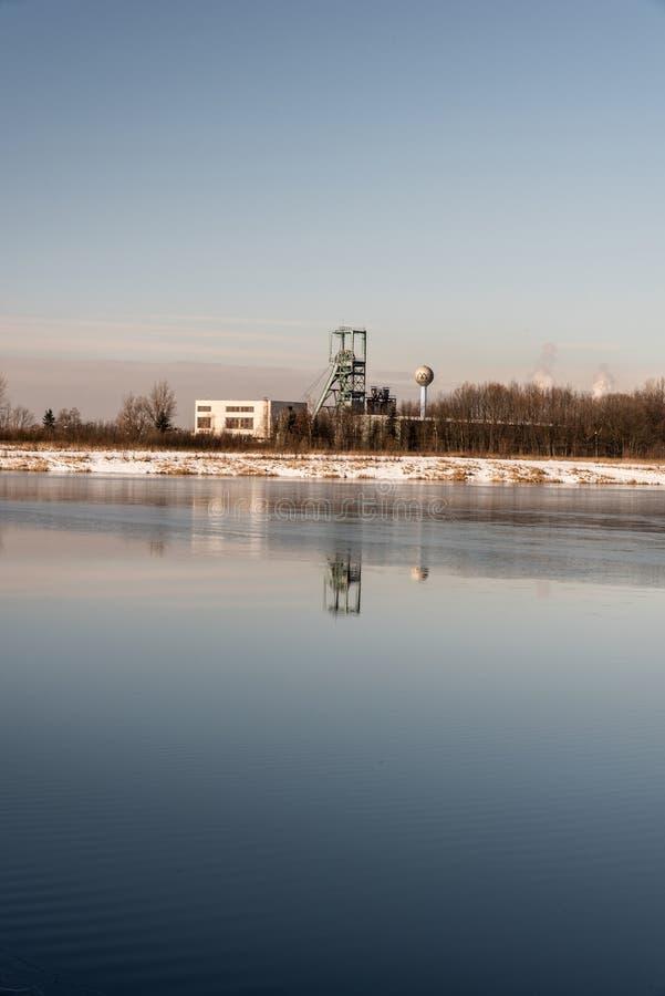 Headframe od Ful Darkov bituminous coal mine reflecting on water fround of Karvinske more lake near Karvina city in Czech republic. Headframe od Ful Darkov stock photo