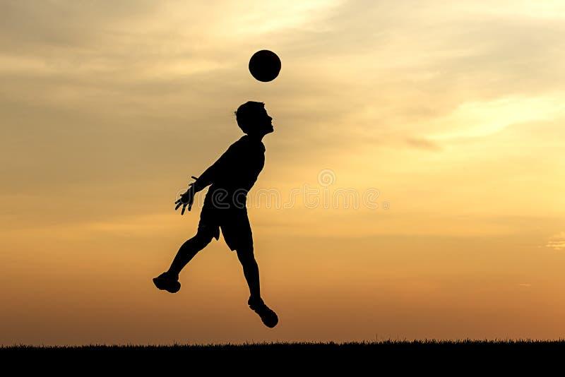 Heading av fotbollbollen på solnedgången royaltyfri foto