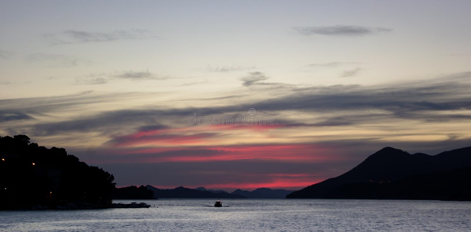 Heading home, Dubrovnik. A small boat heading home to Gruz Port, Dubrovnik. Last rays of sunshine painting the clouds red royalty free stock photo