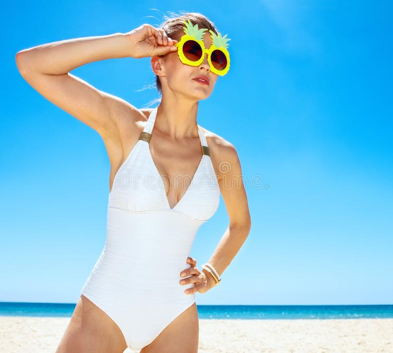 Woman in funky pineapple glasses looking into distance at beach. Heading to white sand blue sea paradise. Woman in white swimsuit and funky pineapple glasses stock photo