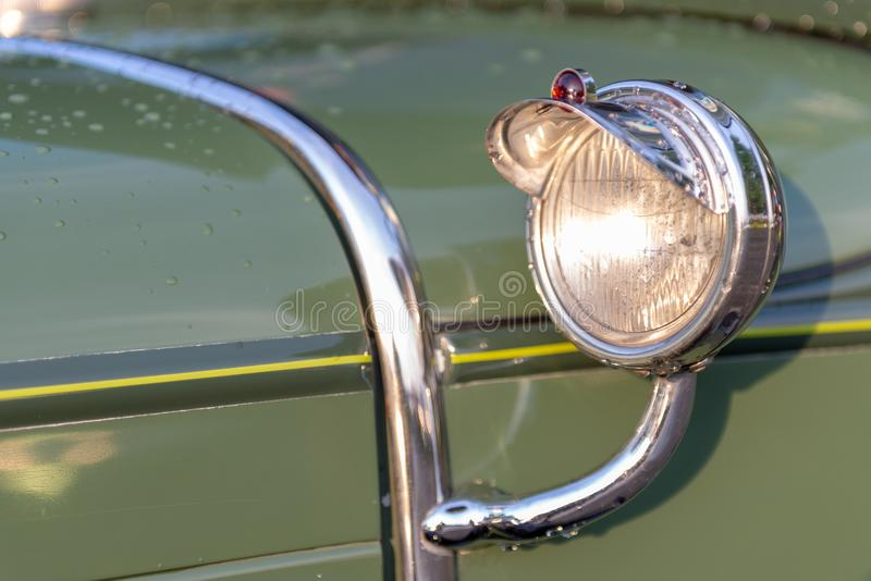 Headlamp and chrome detail on hood of vintage classic oldtimer car. Headlamp and chrome decoration detail on hood of vintage classic oldtimer car stock images