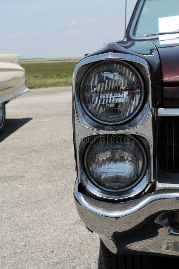 Headlamps. Vertically stacked headlamps belonging to classic Pontiac Tempest GTO. shot at 2014 Memorial Day car show, Tamiami Airport, Miami, Florida royalty free stock photography