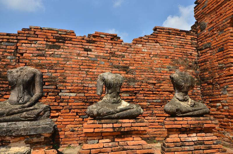 Headless Buddha images on the bases beside red brick wall. Of ancient temple in Thailand royalty free stock photography