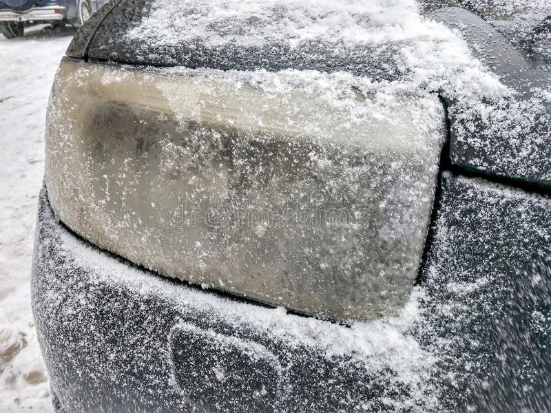 Headlight black car covered with snow and ice. Closeup view royalty free stock image