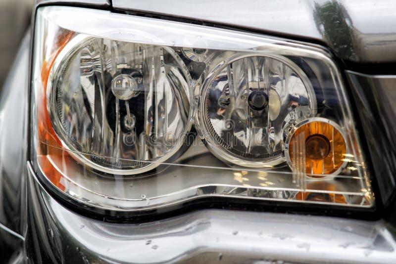 Headlight closeup of grey sporty car stock photography