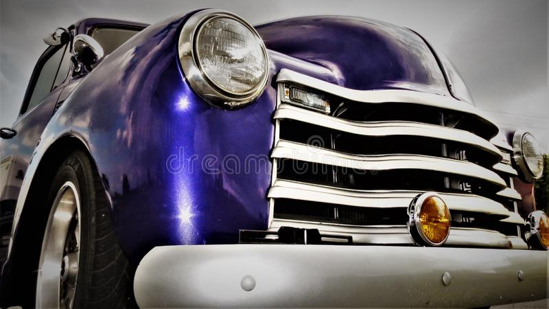 Headlight and Grill of a purple Antique American Pick Up Truck royalty free stock photo