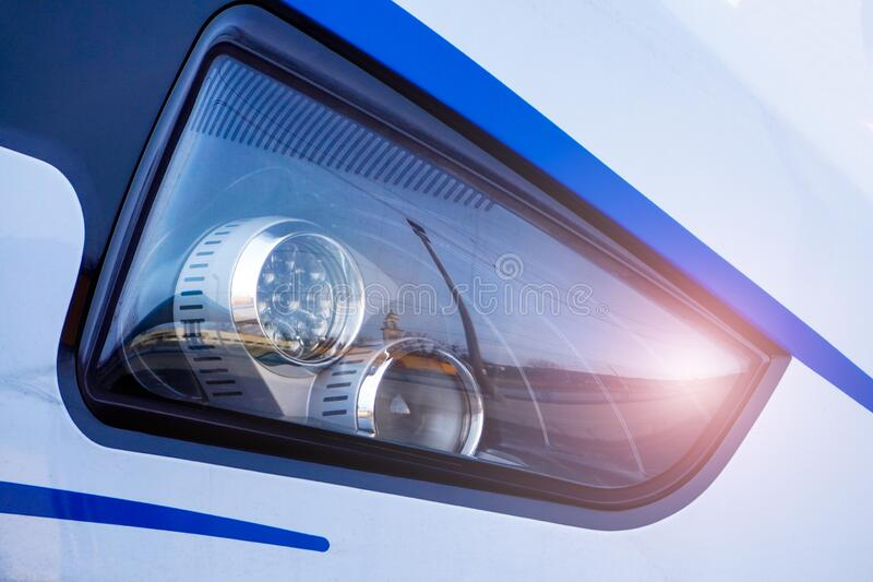 The headlight of a modern high-speed train, with the reflection of a railway station in it. Highlight in the photos. The headlight of a modern high-speed train royalty free stock image