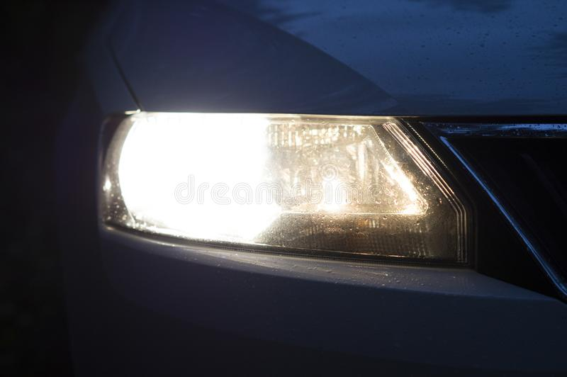 Headlight of a modern passenger car brightly shining in the dark. Luminous headlight of a car under a layer of snow after a snowfall royalty free stock photos