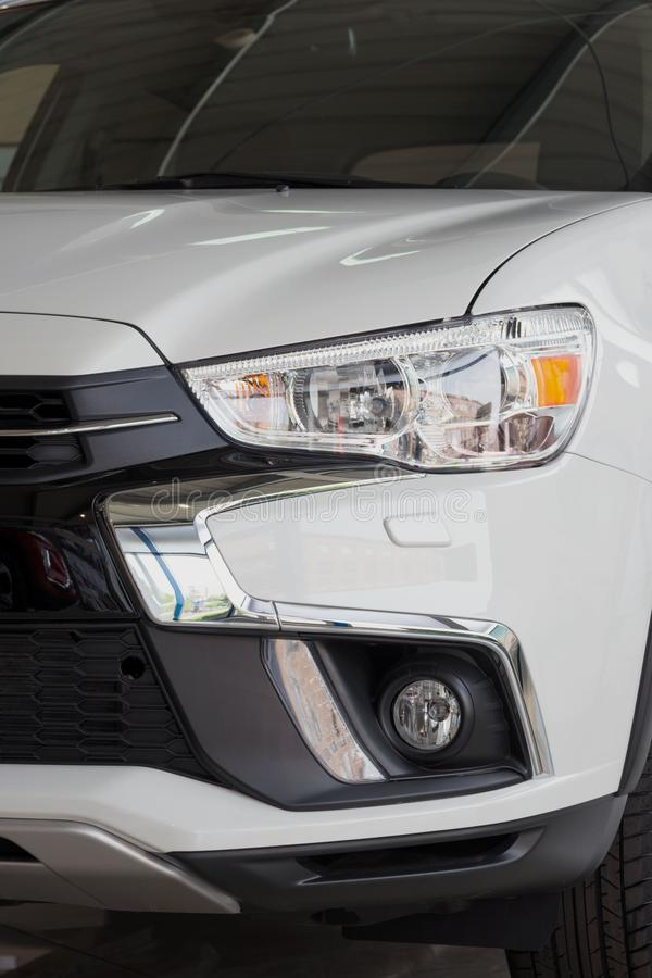 Headlight of a modern white car. Close-up. Detail of automotive lighting system stock images