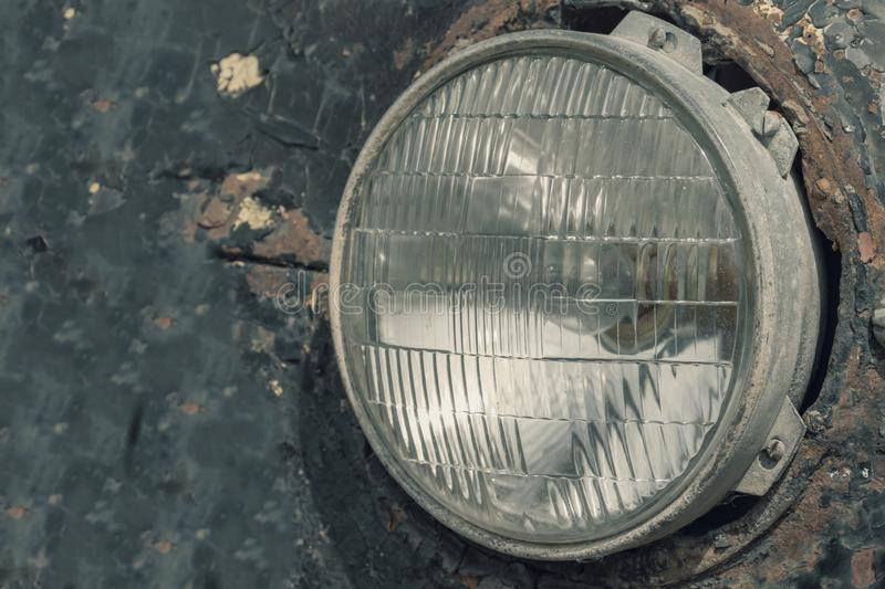 Headlight of an old rusty abandoned car, utilisation and scrap concept stock photography