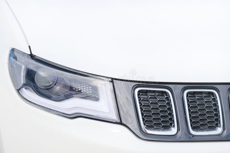 Headlight and radiator of modern white suv car royalty free stock photography