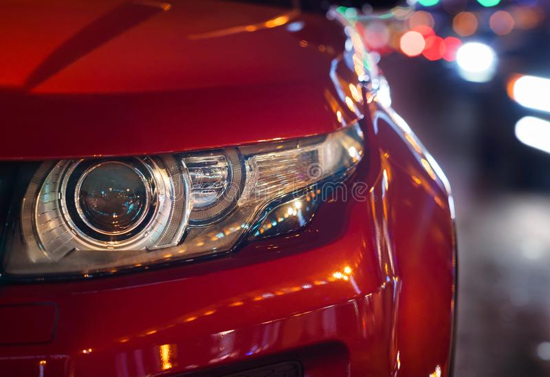 Headlights and hood of sport red car. evening city. Automobile detail close-up stock photos