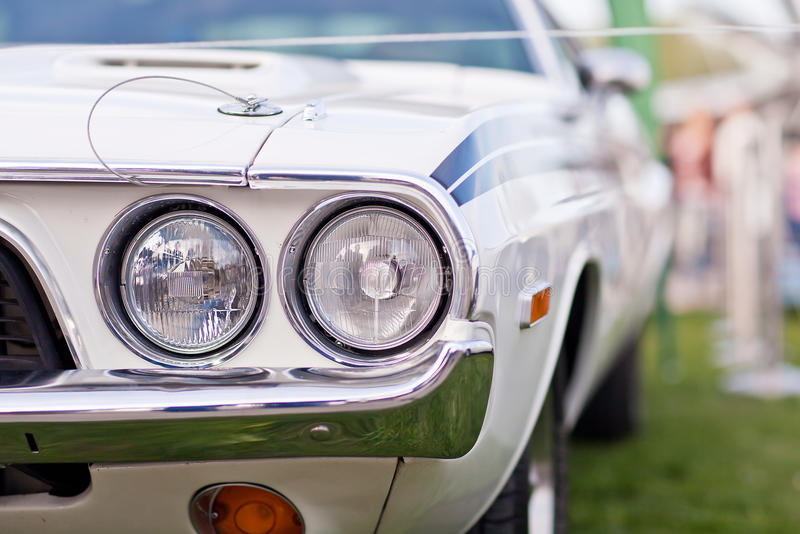 Headlights of old white american muscle car with chrome bumper stock photo