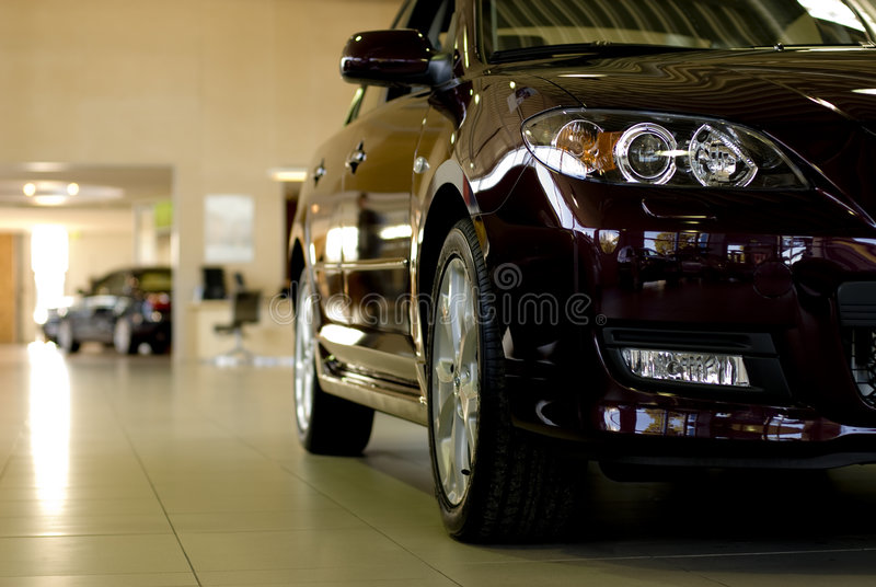 Headlights and side of car. A closeup of the right headlights, side and wheels of a brand new black car in the showroom stock photos