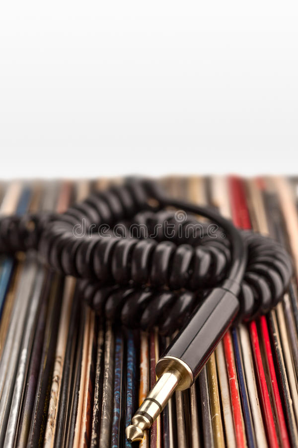 Headphone jack and vinyl records. The retro photo of a 6.3 jack cable of professional audio headphones with vintage vinyl records stock images