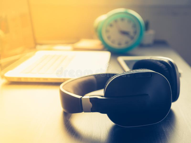 Headphone with Laptop on office desk and sunshine in afternoon. Home related stuffs stock image
