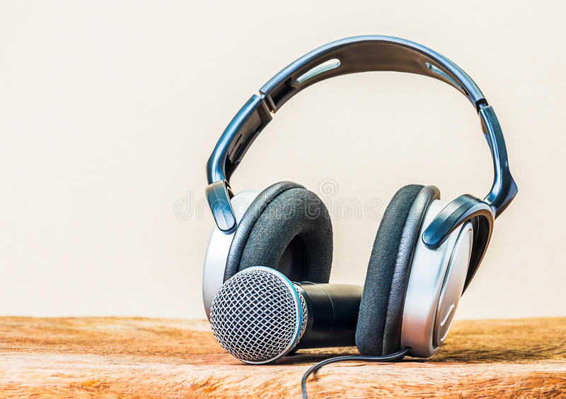 Headphone and microphone. Modern headphone and microphone on wooden background stock image