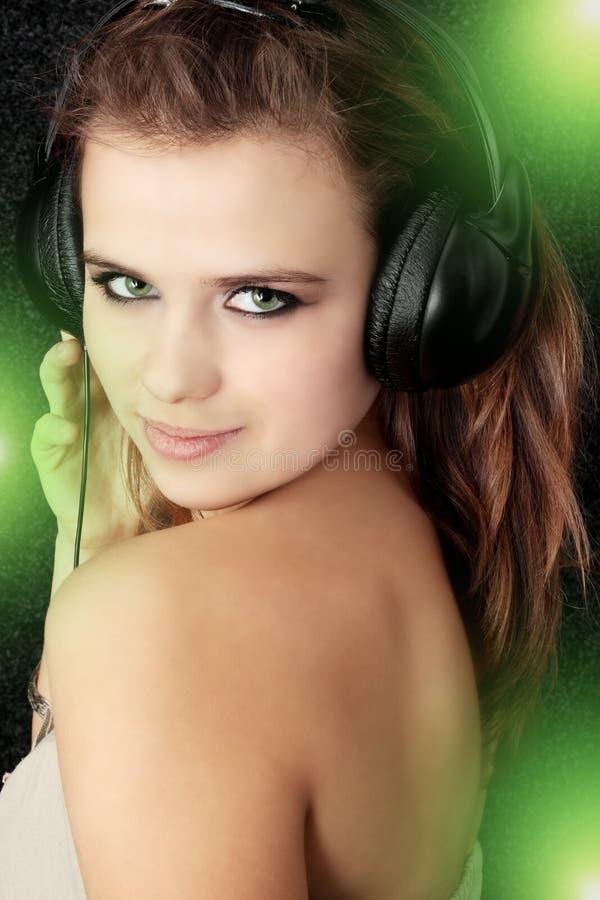In headphones. Beautiful young women listening music in headphones stock photography