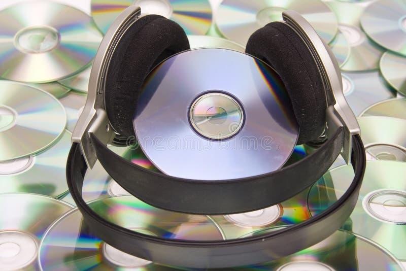 Headphones. Grey and black earphones and compact disc stock photo