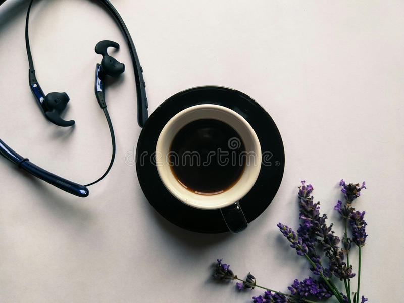 Headphones, Black coffee, purple lavender. Headphones, Black coffee in the little cup and purple lavender flowers on the white background for social media posts royalty free stock photos