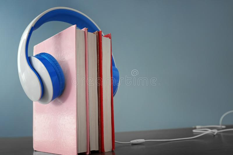 Headphones and books on table. Concept of audiobook stock photography