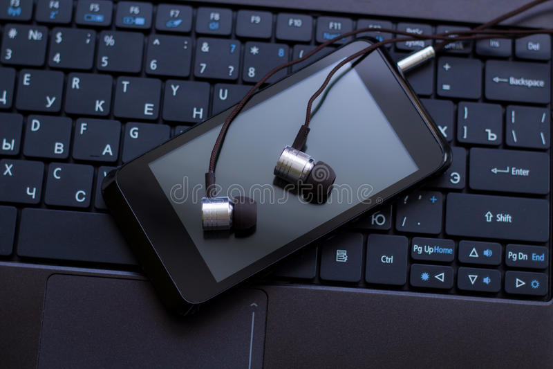 Headphones and cell phone at the keyboard. royalty free stock image