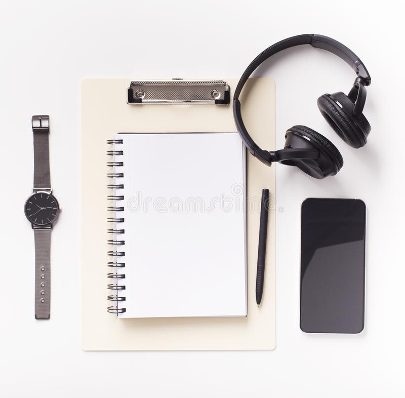 Headphones, cellphone with blank space and notebook on white. Office table with supplies. Headphones, cellphone with blank space and notebook on white background stock photography