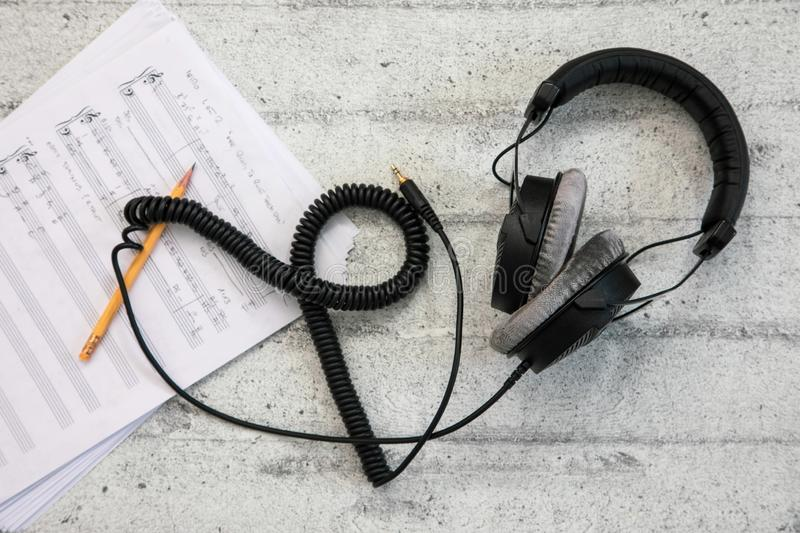 Headphones with cord and music sheet royalty free stock image