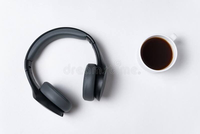 Headphones and cup of coffee on white background, top view. Minimalism stock photos