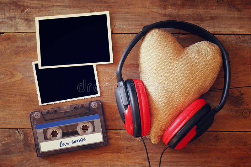 headphones with fabric heart next to empty photo frames royalty free stock photography