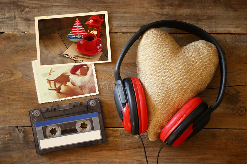 headphones with fabric heart next to photo frames stock photo
