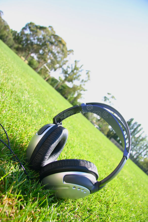 Headphones with grass and sky stock images