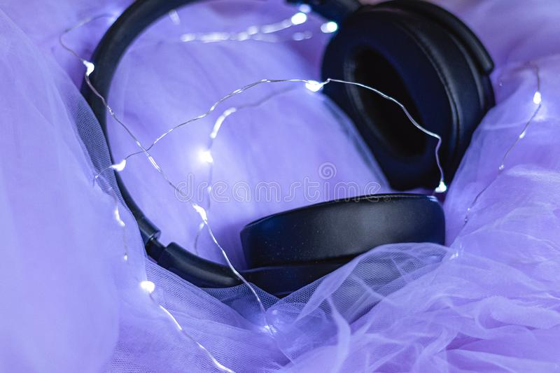 Headphones laying on purple tulle and led lights royalty free stock images