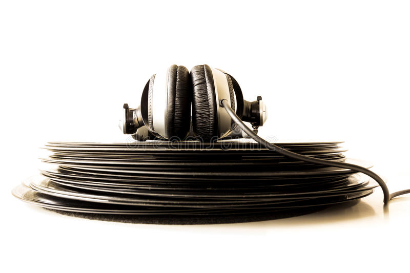 Headphones lying on the stack of vinyl records. Music concept stock photo