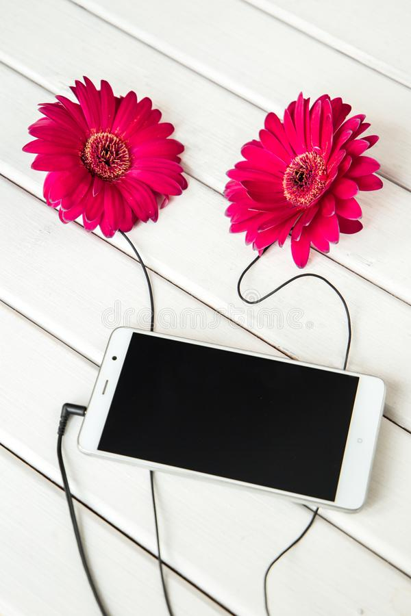 Headphones made frome gerbera flowers and smart phone on wooden table. Top view. vertical royalty free stock photography