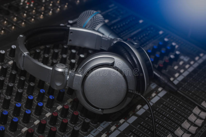 Headphones and Microphone on sound music mixer control panel. royalty free stock images
