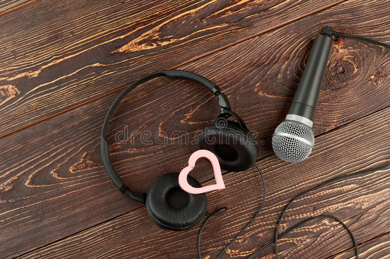 Headphones and microphone on wooden background. stock image