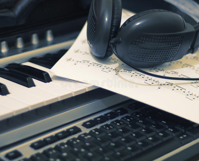 Headphones and music sheet on keyboard royalty free stock photos