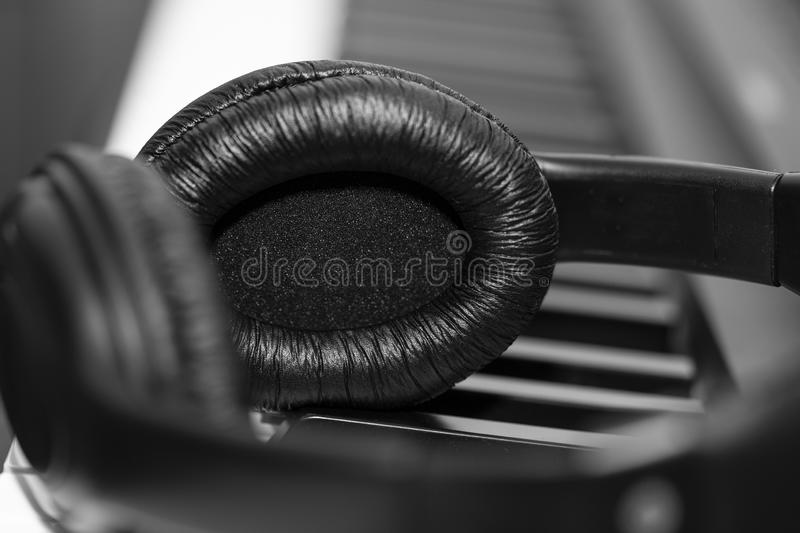 Headphones on musical synthesizer keyboard. Headphones on electronic piano. Musical background royalty free stock images