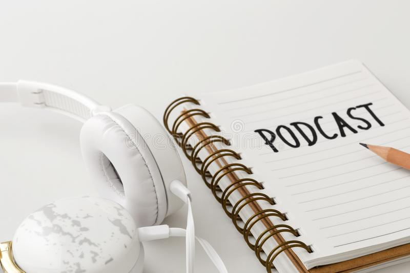Headphones with podcast word on notebook. On white background stock image