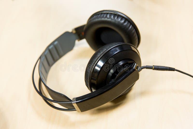 Headphones at recording studio or radio station. Technology, electronics and audio equipment concept - close up of headphones at recording studio or radio royalty free stock images