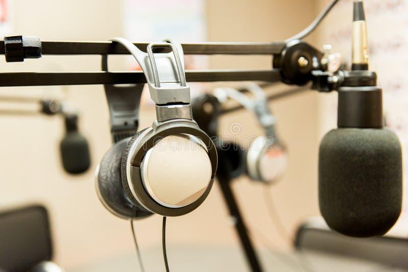 Headphones at recording studio or radio station. Technology, electronics and audio equipment concept - close up of headphones and microphone at recording studio stock photo