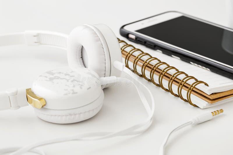 Headphones with smartphone on notebook stock photo