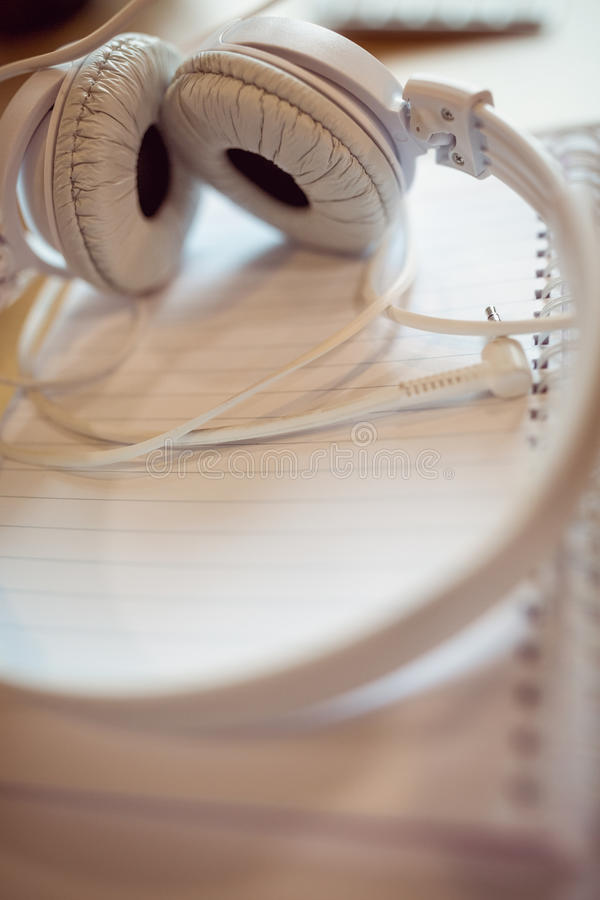 Headphones on spiral notebook. High angle view of headphones on spiral notebook stock photography
