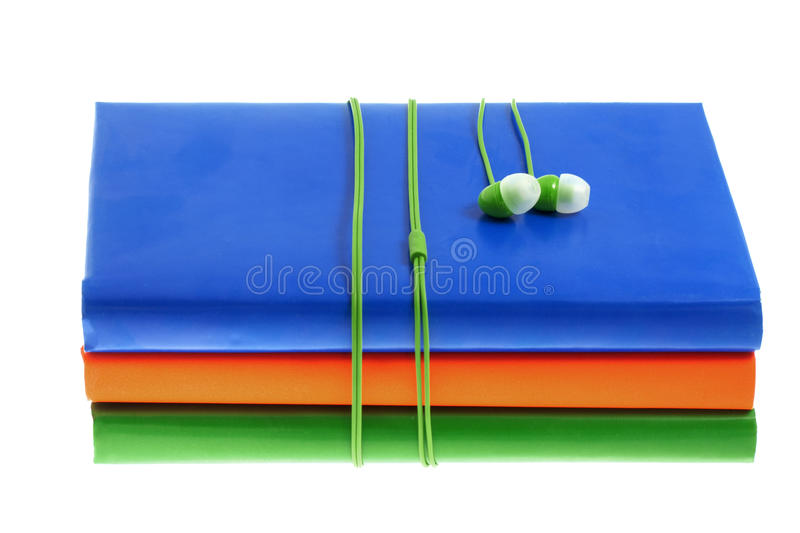 Headphones and stack of multicolored books on a white background. Headphones and stack of multicolored books on the white background royalty free stock image