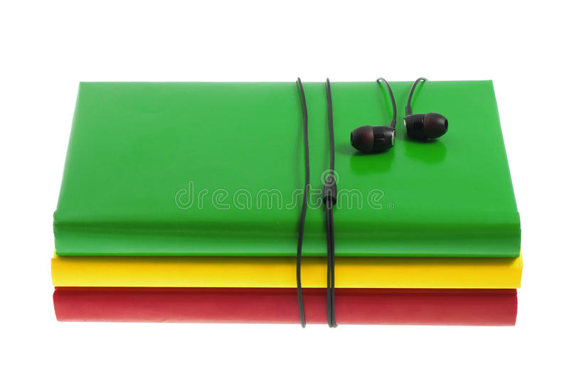 Headphones and stack of multicolored books on a white background. Headphones and stack of multicolored books on the white background stock photo