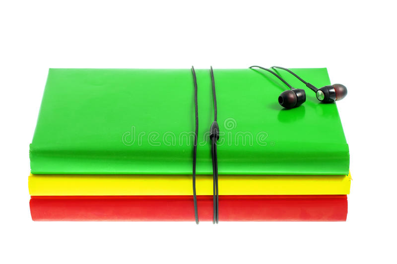 Headphones and stack of multicolored books on a white background. Headphones and stack of multicolored books on the white background stock photography