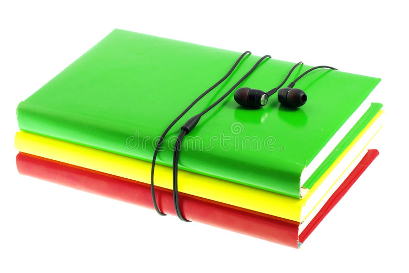 Headphones and stack of multicolored books on a white background. Headphones and stack of multicolored books on the white background royalty free stock photos