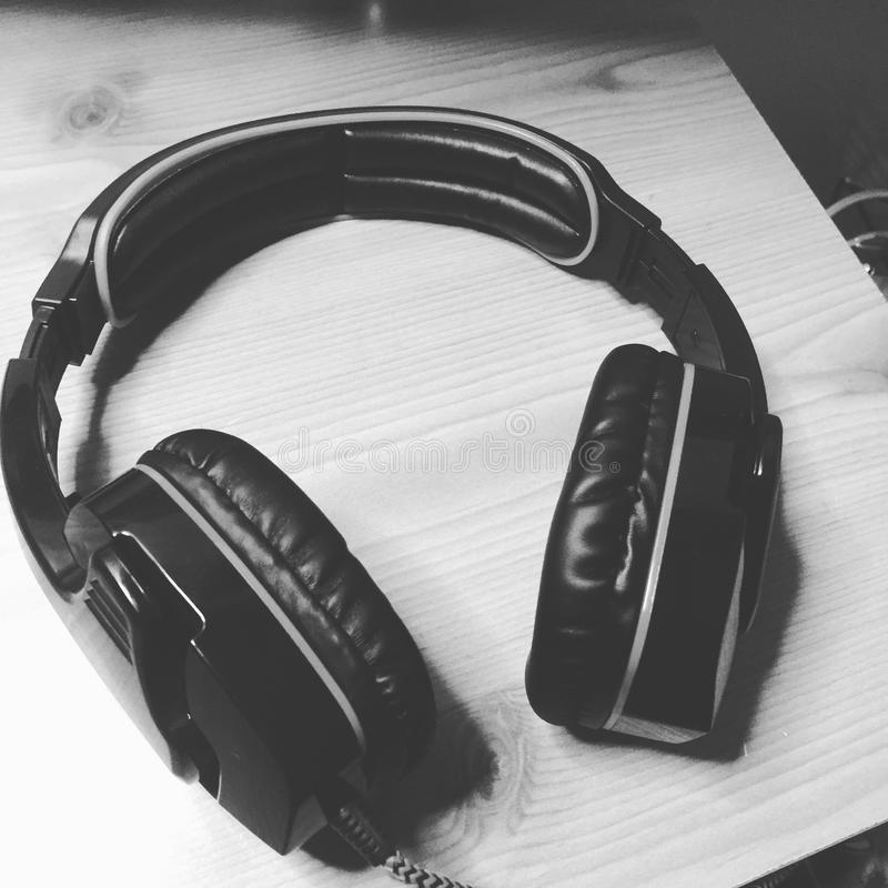 Headphones on wooden desk in black and white royalty free stock photography