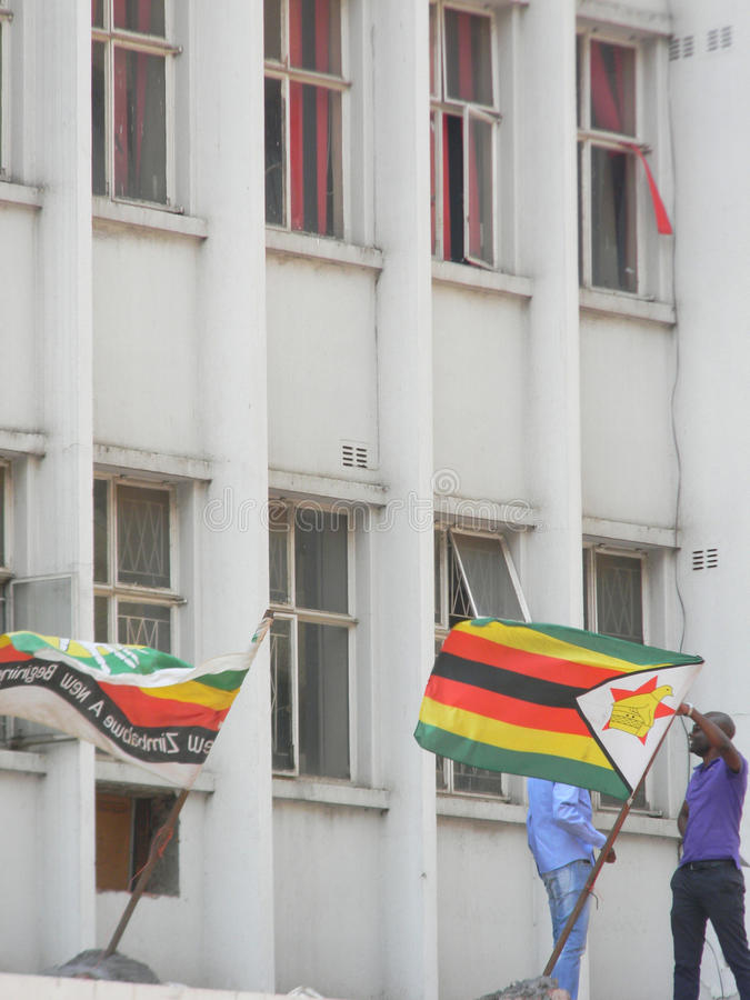 Headquarters of M. D. C party in Harare, Zimbabwe. Harare, Zimbabwe, November 9 2015. The flag of the Movement for Democratic Party (MDC) beside the Zimbabwe royalty free stock photo